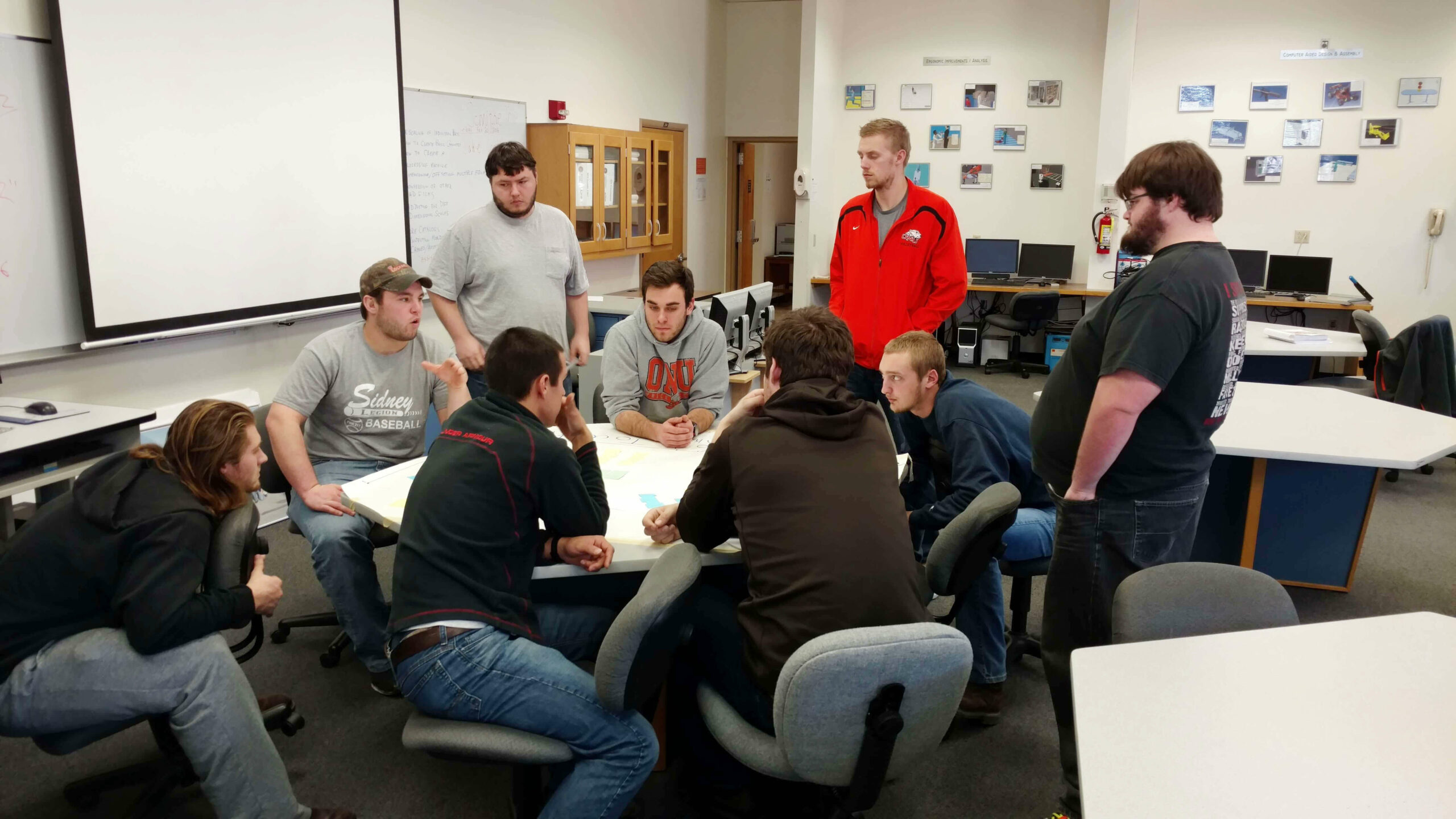 nine Ohio Northern University students working on a factory simulation project