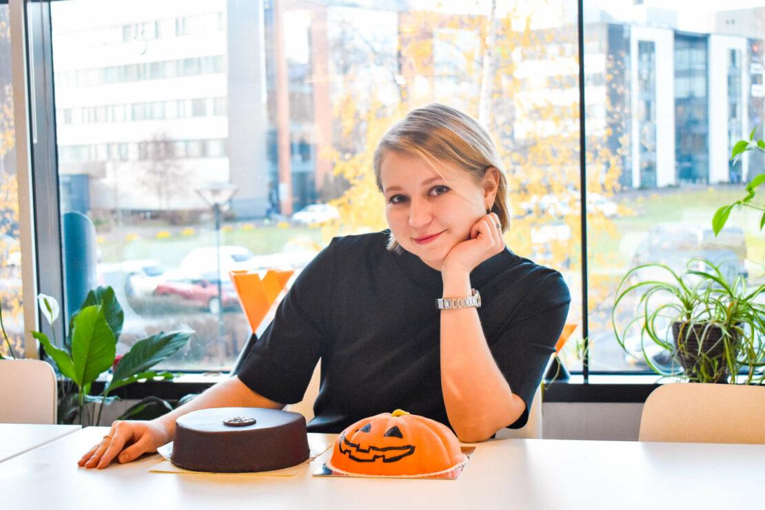 Sales Coordinator Olga sitting at a table smiling