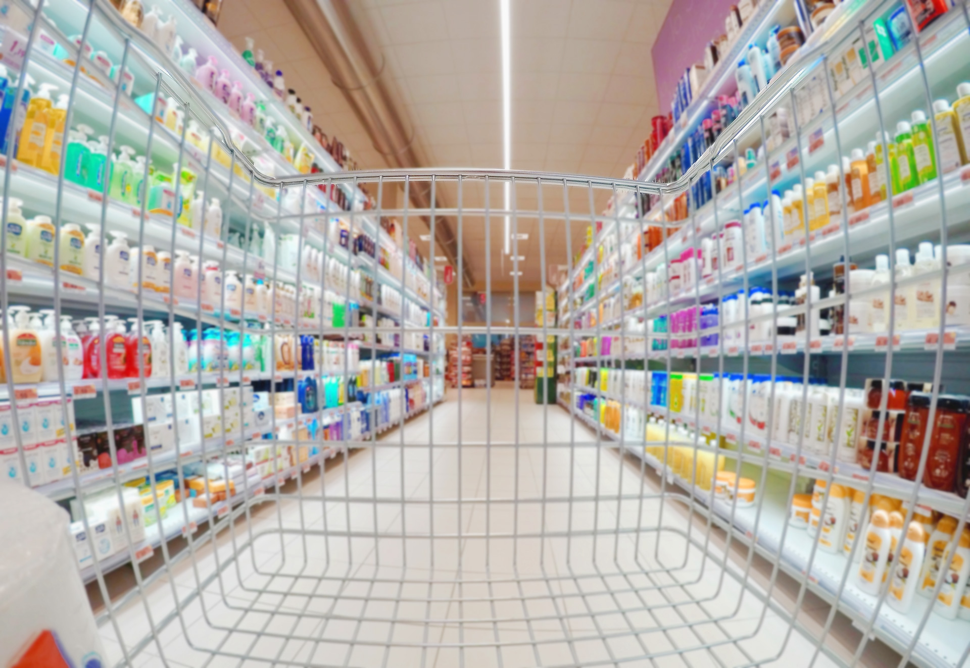 Empty shopping cart between shelves full of products