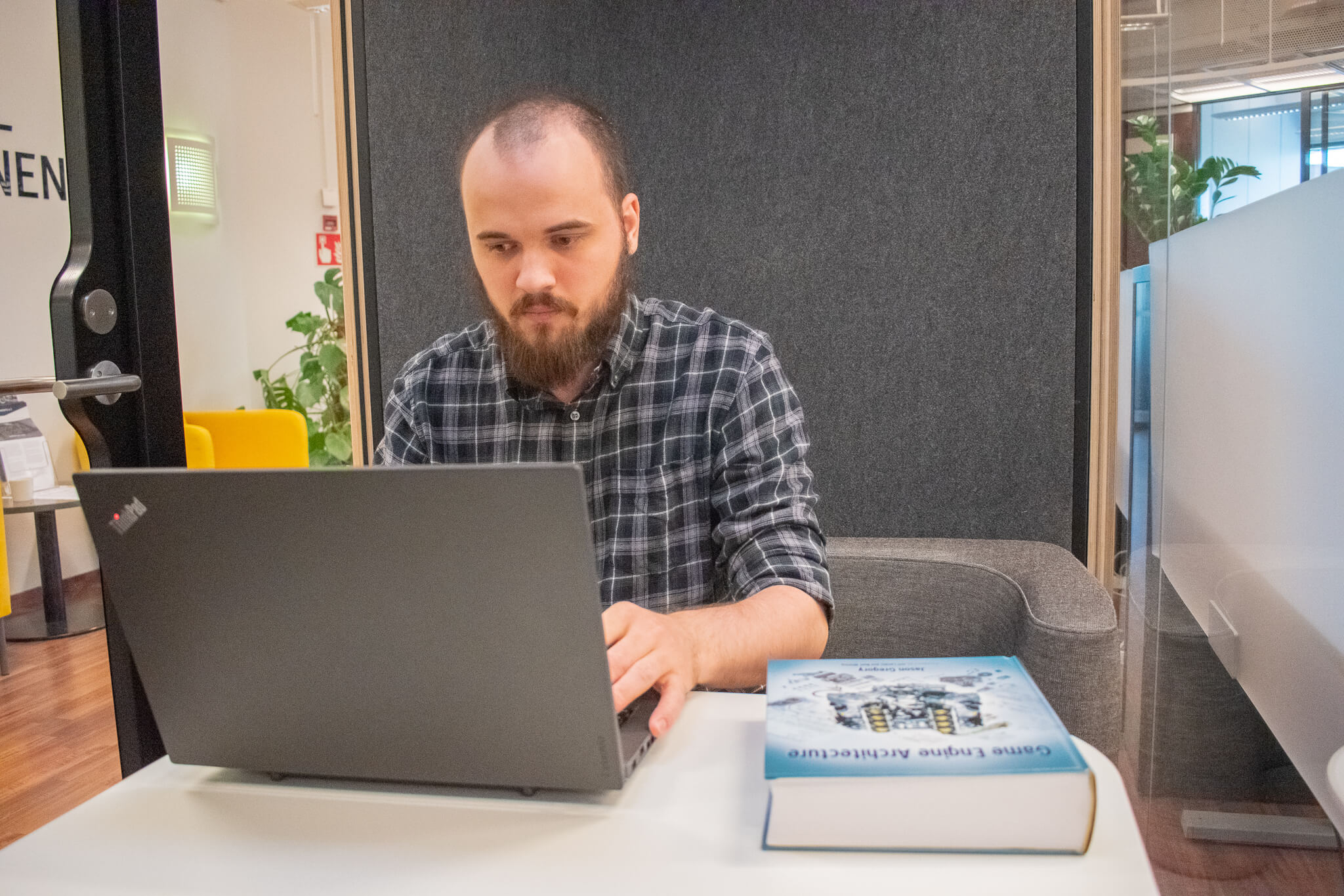 Developer Jevgeni working on simulation software on a laptop with a closed book on the table
